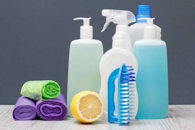 Plastikowe butelki z płynem do mycia naczyń, płynem do czyszczenia szkła i płytek, detergentem do kuchenek mikrofalowych i kuchenek, workami na śmieci, pędzelkiem i cytryną na szarym tle. koncepcja mycia i czyszczenia.