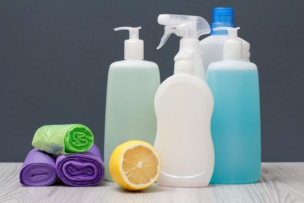 Plastikowe butelki z płynem do mycia naczyń, płynem do mycia szyb i płytek, detergentem do kuchenek mikrofalowych i kuchenek, workami na śmieci i cytryną na szarym tle. koncepcja mycia i czyszczenia.