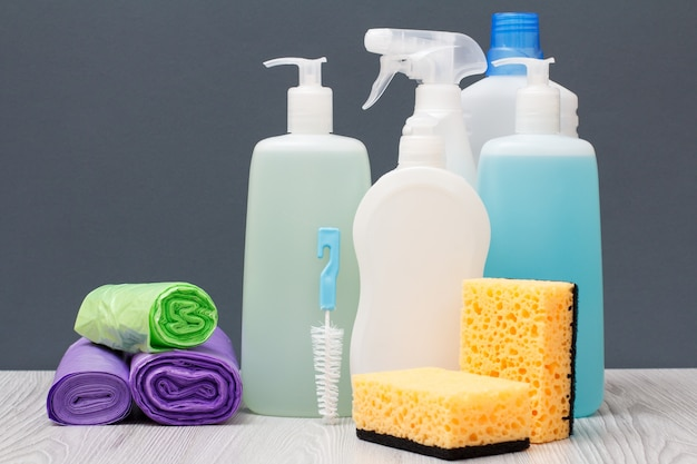 Plastikowe butelki z płynem do mycia naczyń, płynem do mycia szyb i płytek, detergentem do kuchenek mikrofalowych i kuchenek, worków na śmieci i gąbek na szarym tle. koncepcja mycia i czyszczenia.