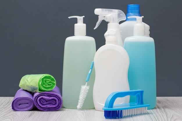 Plastikowe butelki z płynem do mycia naczyń, płynem do mycia szyb i płytek, detergentem do kuchenek mikrofalowych i kuchenek, worków na śmieci i pędzli na szarym tle. koncepcja mycia i czyszczenia.
