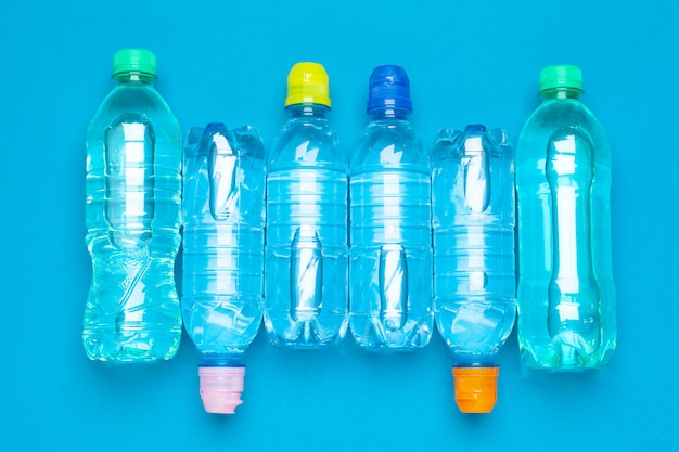 Plastikowe butelki z wodą w różnych kolorach na stole