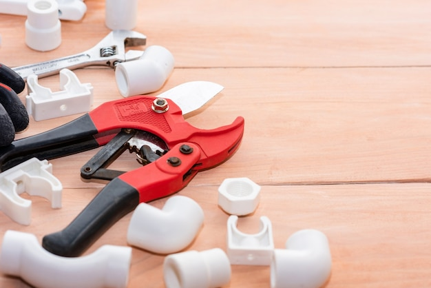 Plastikowe części na drewnianym stole do instalacji wodociągowej.