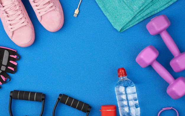 Plastikowe fioletowe hantle, odzież sportowa, woda, różowe trampki i słuchawki bezprzewodowe