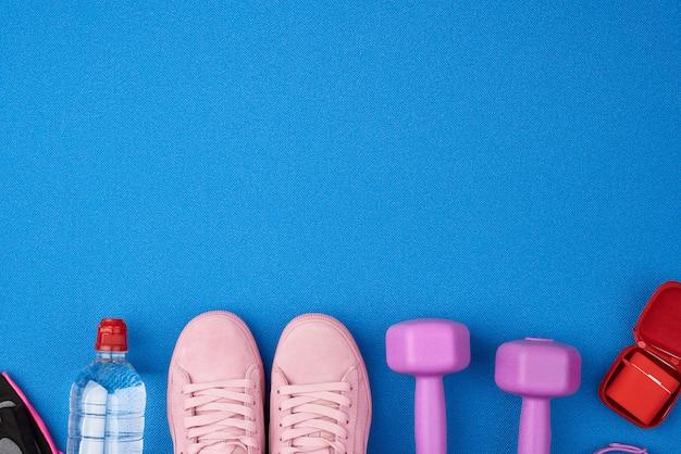 Plastikowe fioletowe hantle, odzież sportowa, woda, różowe trampki z maty sportowej
