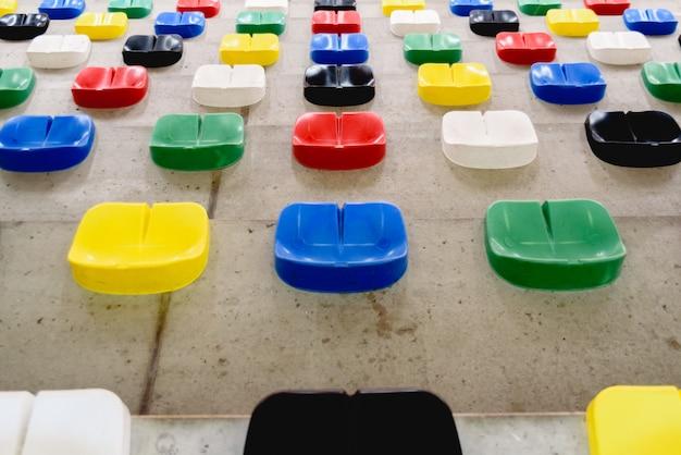 Plastikowe fotele w jaskrawych kolorach bez publiczności siedzącej w hali sportowej.
