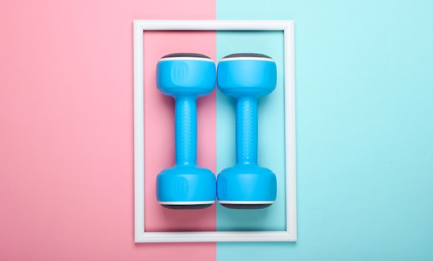 Plastikowe hantle na różowo-niebieskiej pastelowej powierzchni z białą ramką