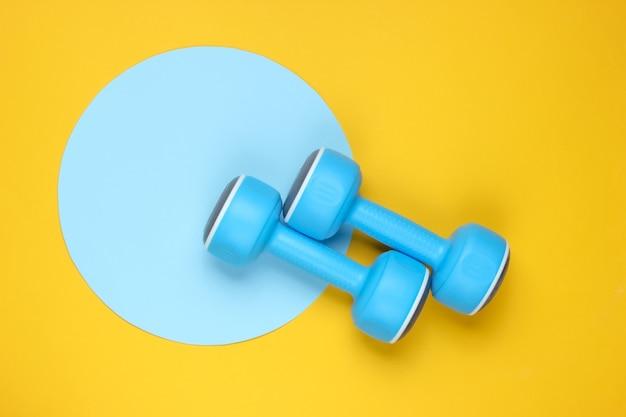 Plastikowe hantle na żółtym tle z niebieskim pastelowym kółkiem. widok z góry. minimalistyczna koncepcja sportu. widok z góry