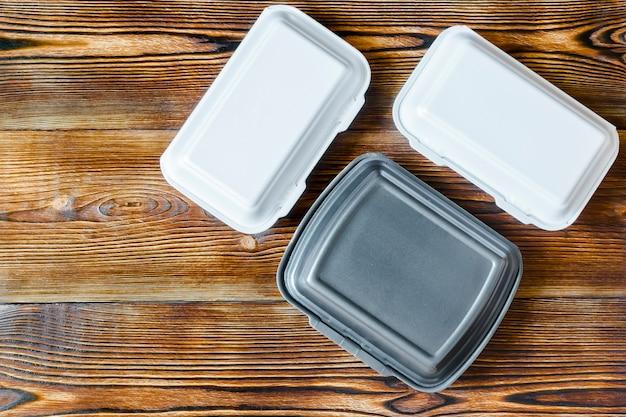 Plastikowe jednorazowe pojemniki na żywność leżące na drewnianym tle rustykalnym z miejsca na kopię gotowy do zamówienia. usługa dostawy żywności z koncepcji restauracji.