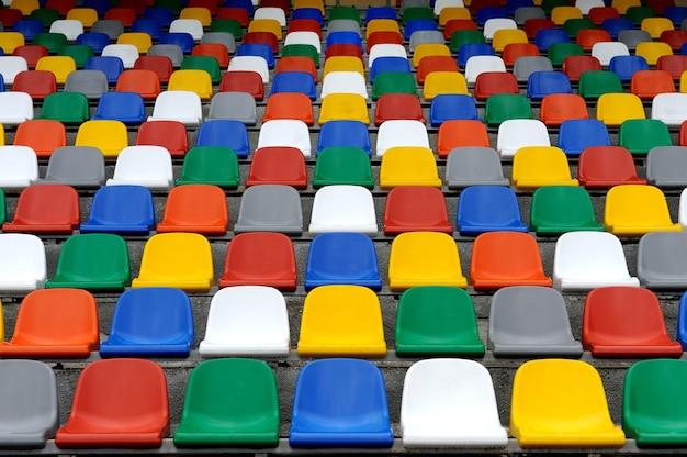 Plastikowe kolorowe krzesła stoją na stadionie