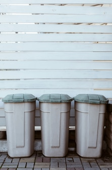 Plastikowe kosze na śmieci na ścianie z drewnianych desek na podwórku