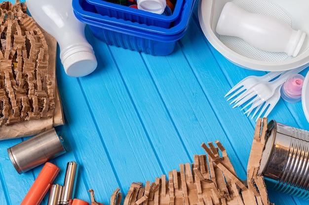 Plastikowe naczynia kuchenne, metalowe puszki, odpady papierowe i kartonowe na niebieskiej powierzchni