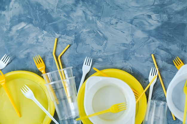 Plastikowe naczynia na niebieskim tle. skopiuj miejsce. zanieczyszczenie środowiska.