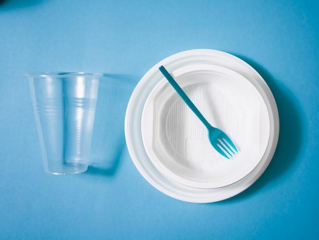 Plastikowe naczynia, naczynia jednorazowe, talerze, szklanki, łyżki, widelce na niebieskim tle. w trosce o środowisko. problemem jest recykling. ponowne użycie, bezpieczna planeta, koncepcja ochrony środowiska. śmieci.