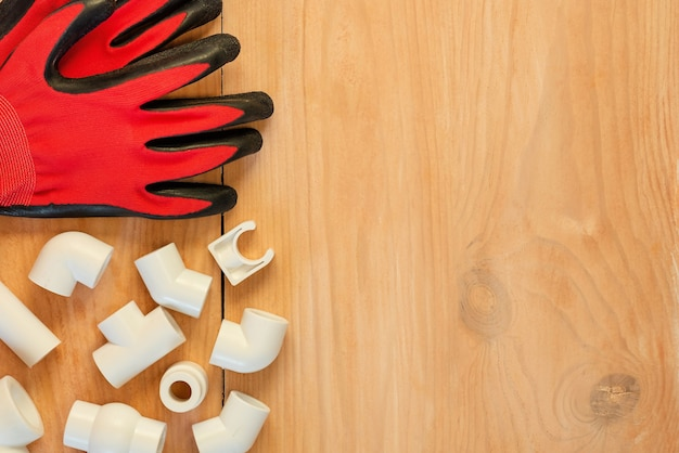 Plastikowe narzędzie do cięcia rur i rękawice na drewnianym stole, widok z góry