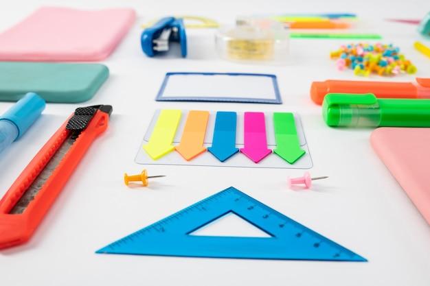 Plastikowe niewolnictwo. niebieska linijka stojąca z kolorowymi zakładkami z nożem do papieru na białej powierzchni