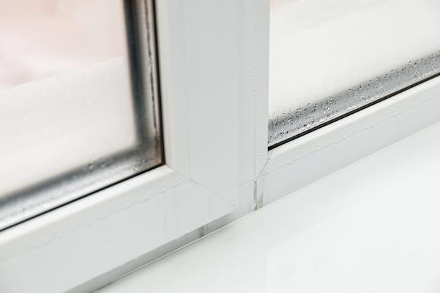 Plastikowe okienko z kondensacją wilgoci i wody na szkle. zła wentylacja w domu podczas zimnej pogody
