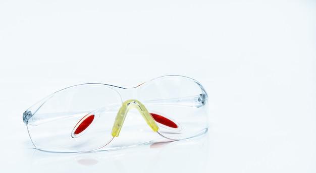 Plastikowe okulary ochronne na białym tle. okulary ochronne dla ochronnego oka pracownika na budowie lub w fabryce. narzędzia bezpieczeństwa i ochrony.