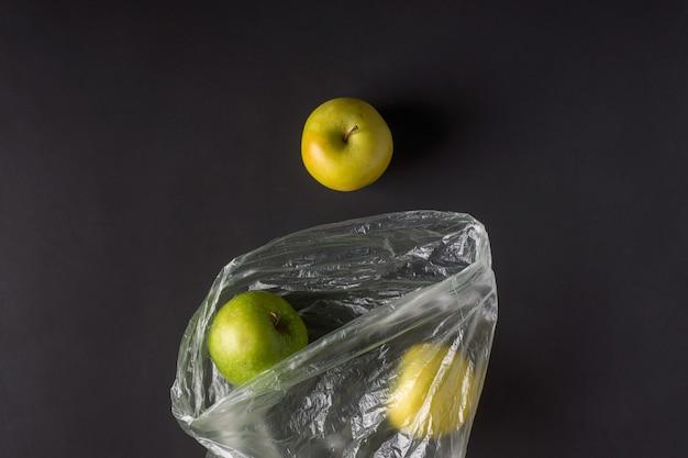 Plastikowe opakowania jednorazowego użytku wydają zielone jabłka w plastikowych torebkach w ciemności