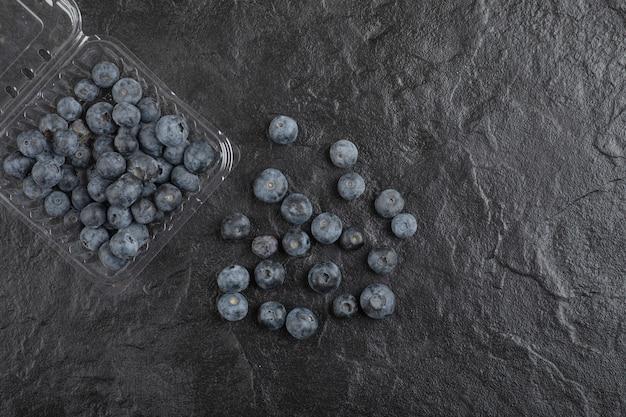 Plastikowe opakowanie pysznych świeżych jagód na czarnej powierzchni