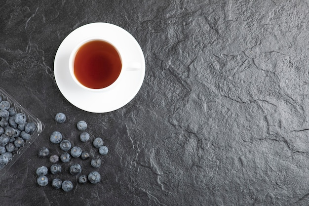 Plastikowe opakowanie pysznych świeżych jagód z filiżanką gorącej herbaty