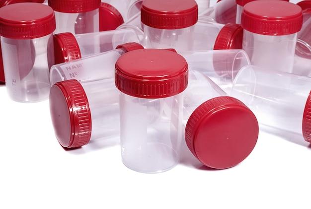 Plastikowe pojemniki medyczne z czerwonymi nakrętkami