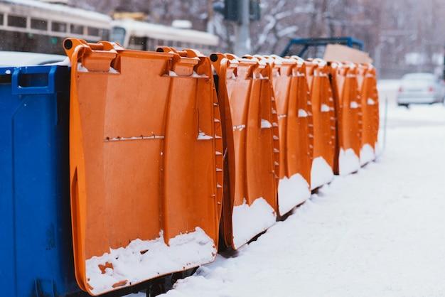 Plastikowe pojemniki na śmieci stoją w szeregu wzdłuż drogi