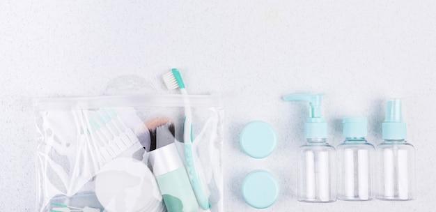 Plastikowe pojemniki, szczoteczka do zębów i pędzel do makijażu. zestaw podróżny flat lay