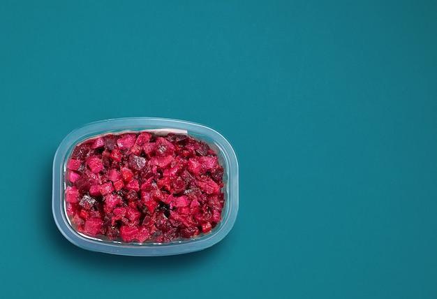 Plastikowe pudełko sałatki warzywnej z buraków z olejem na niebieskim tle, widok z góry