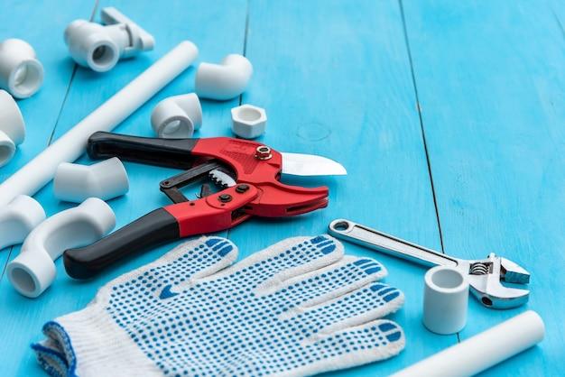 Plastikowe rury do instalacji wodnej, narzędzia do cięcia rur, klucz, narożniki, uchwyty, kurki, adaptery i rękawice robocze na jasnoniebieskim tle.