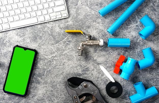 Plastikowe rury do instalacji wodnej, narzędzie do cięcia rur, kran, smartfon, klawiatura.