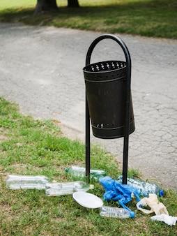 Plastikowe śmieci w pobliżu metalowy kosz w parku