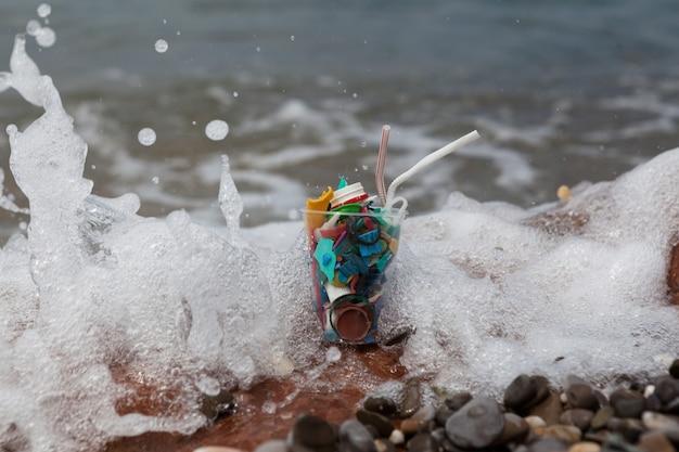 Plastikowe śmieci z morza w plastikowym jednorazowym kubku koncepcja niebezpieczny koktajl morski