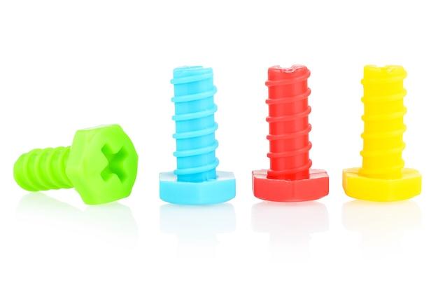 Plastikowe śruby w różnych kolorach ułożone są w rzędzie na białym tle.