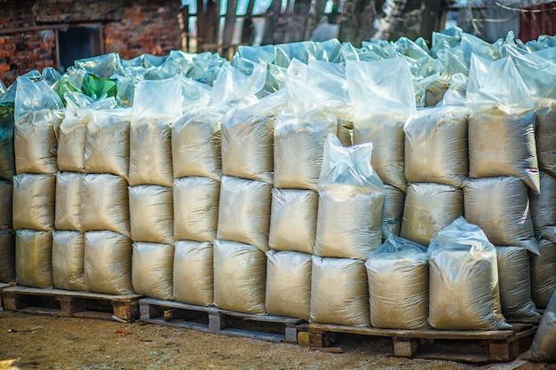 Plastikowe torby z piaskiem i ziemią stoją w rzędach jeden na drugim