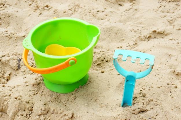 Plastikowe wiaderko z zabawkami i niebieskie grabie do piasku na piasku