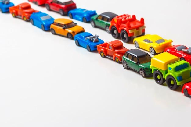 Plastikowe, wielokolorowe samochodziki są ustawione w linii na białym tle