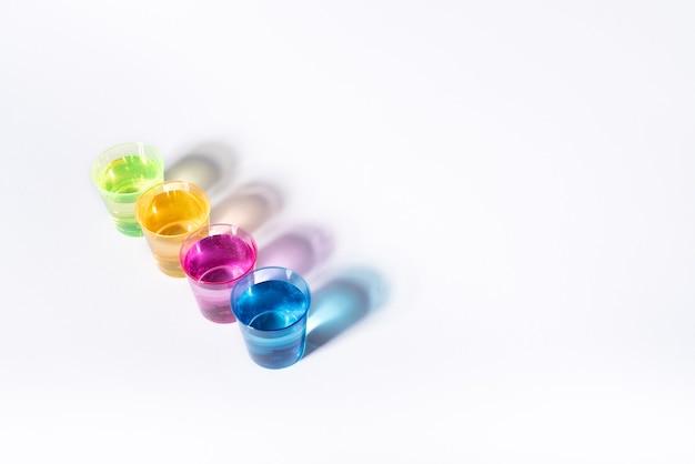 Plastikowe wielokolorowe szklanki z płynem na białej powierzchni z refleksami.