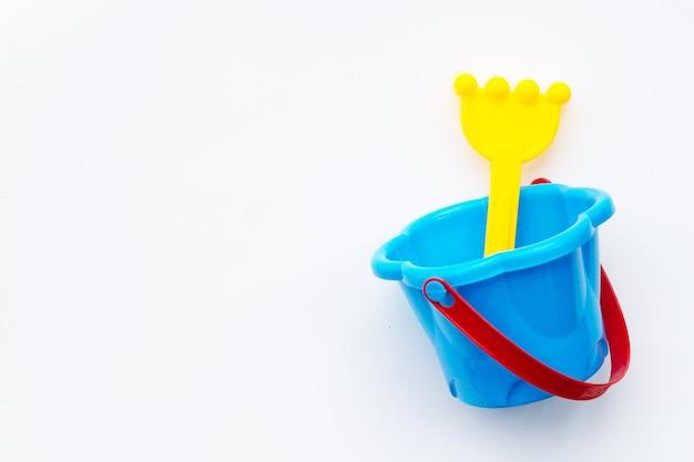 Plastikowe zabawki, łopata w wiadrze do piasku na białej powierzchni.