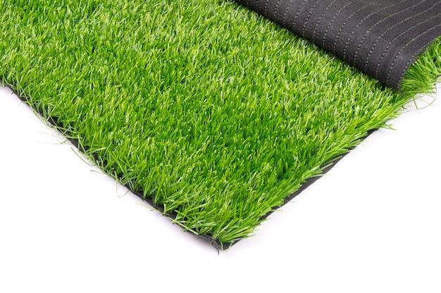 Plastikowe zielona trawa na białym tle z bliska.