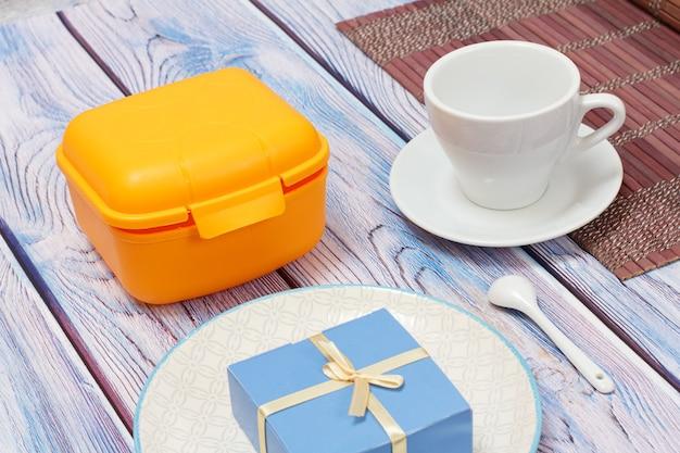 Plastikowe żółte pudełko na lunch, talerz i filiżanka ze spodkiem na drewnianym tle.