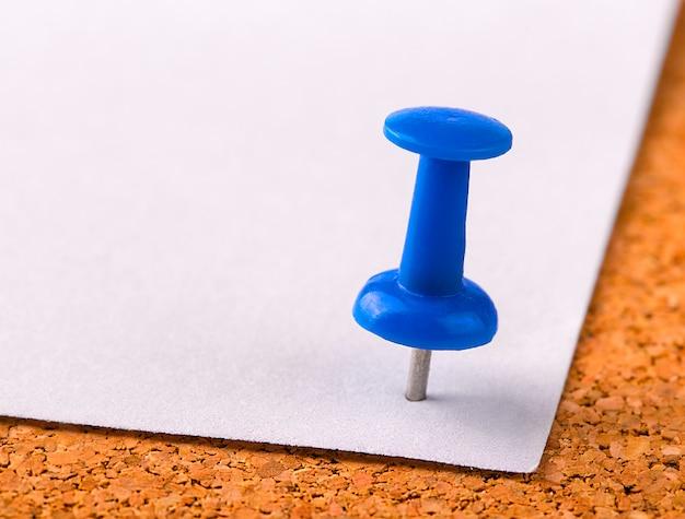 Plastikowy guzik z igłą wbity w żelazny arkusz białego papieru na drewnianym korku