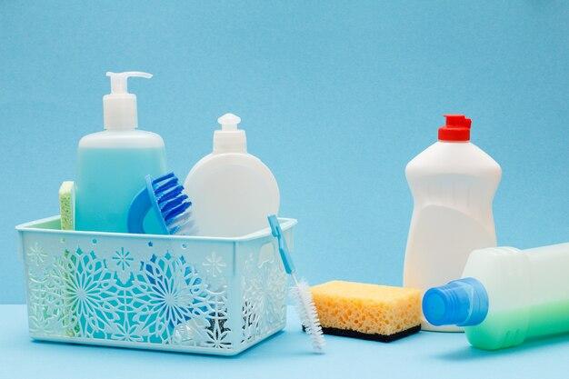 Plastikowy kosz, butelki płynu do mycia naczyń, środek do czyszczenia szkła i płytek, szczotki, worki na śmieci na niebieskim tle. koncepcja mycia i czyszczenia.