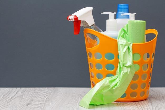 Plastikowy kosz z workami na śmieci, butelkami płynu do mycia naczyń, płynem do czyszczenia szkła i płytek, detergentem do kuchenek mikrofalowych i pieców na szarym tle z miejscem na kopię. koncepcja mycia i czyszczenia.