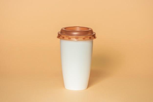 Plastikowy kubek do kawy z brązową pokrywką na białym tle na beżowym tle ze ścieżką przycinającą, makieta dla twojego projektu