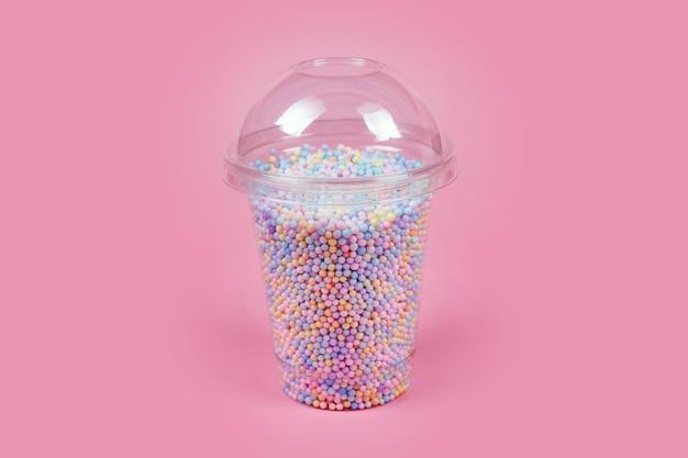 Plastikowy kubek na wynos z kopułką na zimne napoje wypełniony kolorowymi kulkami cukru