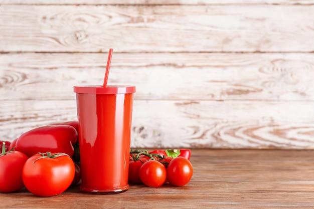 Plastikowy kubek zdrowego smoothie z pomidorami i papryką na drewnianej powierzchni