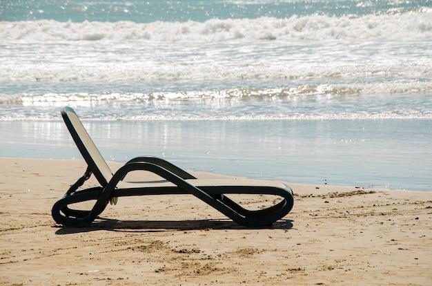 Plastikowy leżak plażowy stoi na piaszczystej plaży na skraju wody na tle fal morskich.
