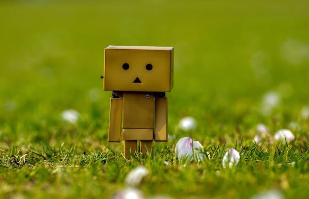 Plastikowy model, który wygląda jak kartonowe pudła bawiące się na trawie wśród rozsypanych w parku kwiatów wiśni