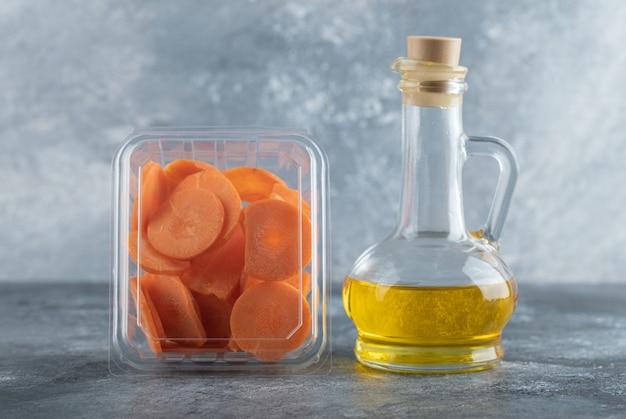 Plastikowy pojemnik pełen plasterków marchwi i butelki oleju na szarym tle.