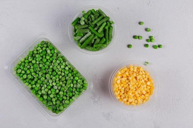 Plastikowy pojemnik z różnymi organicznymi mrożonymi warzywami na białym betonowym stole. zielony groszek, słodka kukurydza i pokrojona zielona fasolka w pudełku